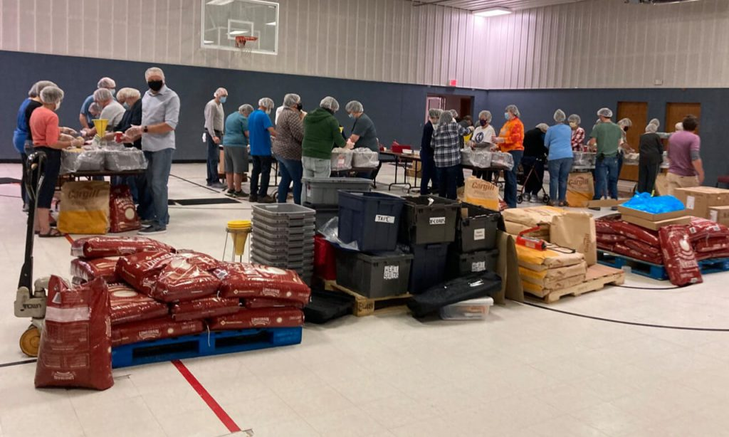 Gym full of people doing a meal pack event.